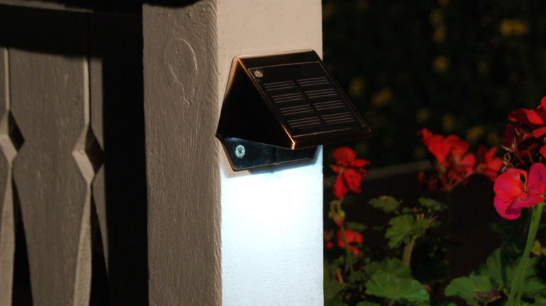 A copper-colored solar rail light from Classy Caps illuminates a white deck post and rail with red flowers in the background