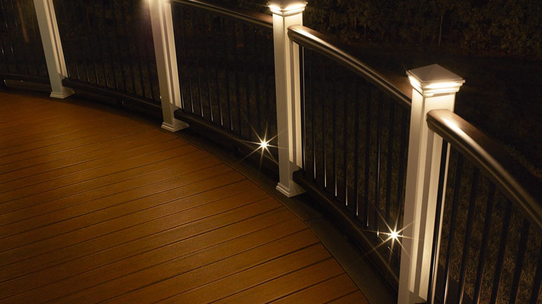 Curved Trex Transcend Railing is illuminated by LED Pyramid Post Cap Lights and the perimeter of the deck is outlined with Recessed LED Dot Deck Lights from Trex DeckLighting