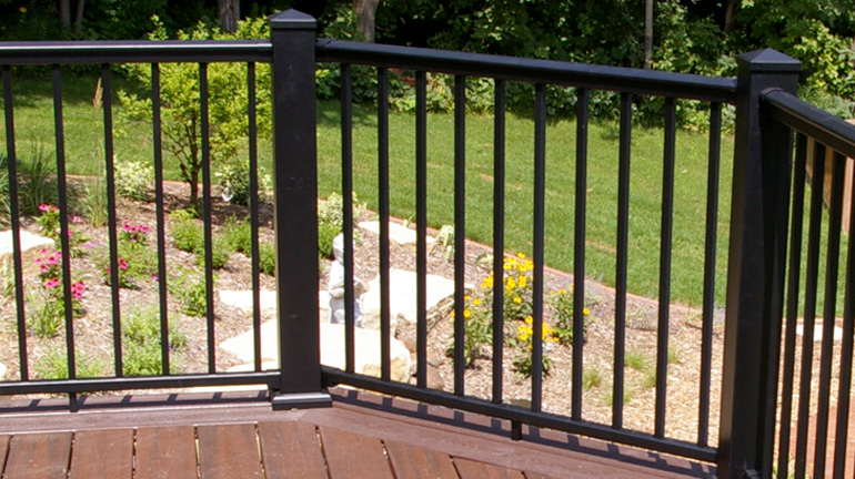 Overlooking a hillside landscaped with shrubbery and flowers, a brown composite deck is outfitted with Textured Black Afco Aluminum Railing with square balusters and 4