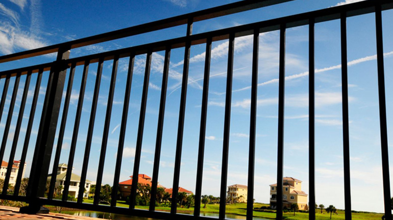 Bright blue sky and green grass are visible through the square aluminum pickets of the Westbury Riviera Aluminum Railing System installed to overlook small pond