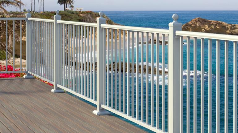 AL13 Pro Rail in white borders a teak deck near the ocean.