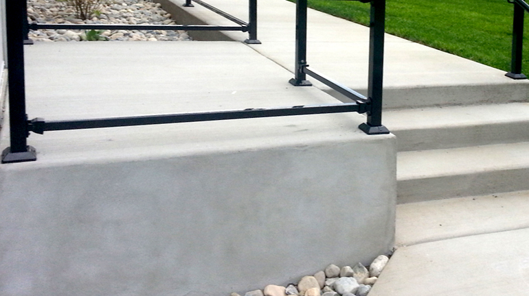 Fortress Iron 2-Piece Post Skirts installed with iron safety handrail on concrete steps