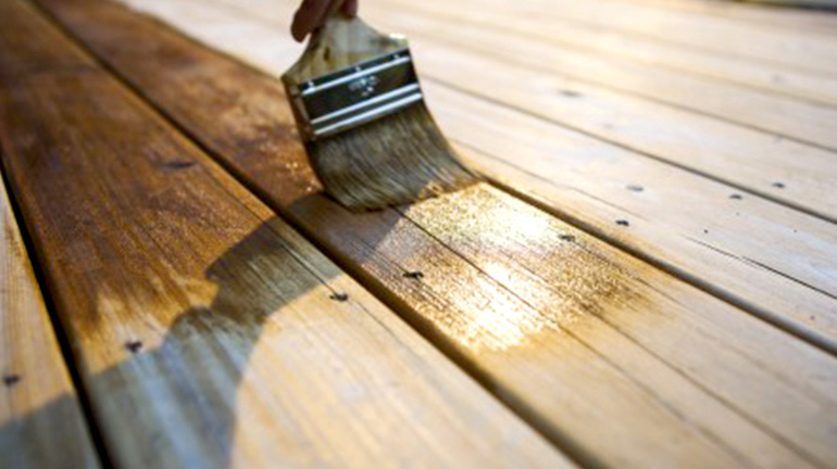 Close-up shot of a homeowner applying stain to a deck board using a small brush