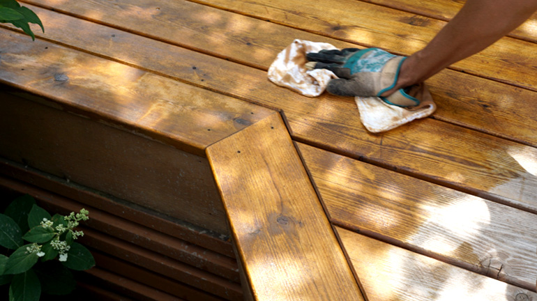 A DecksDirect employee applies Cedar Oil to a cedar deck.