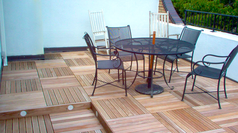 Terrace deck with bistro table, rocking chairs, and hardwood deck tiles from Bison Innovative Products