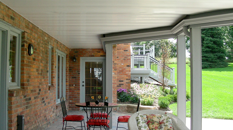 Installing a Zip-Up Under Deck Drainage System and Ceiling in white allows homeowners to use a bistro table with red chairs and a wicker lounge chair on the patio beneath their 2nd story deck.