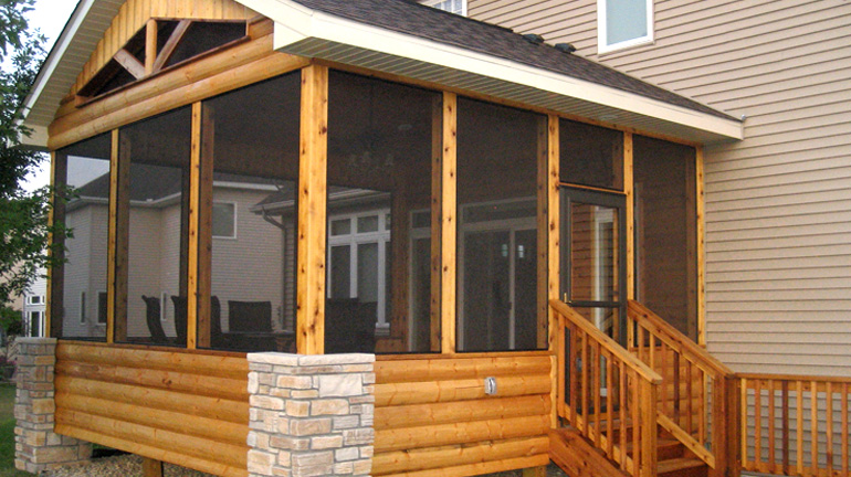 Log cabin style screen porch addition to beige house features SCREENEZE® to keep pests out