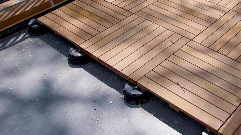 A deck is partially installed on a roof membrane using Bison Low Adjustable Deck Supports and Hardwood Deck Tiles