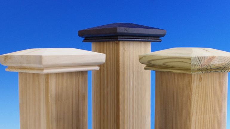 Three hand-crafted Acorn wooden post caps sit on top of 4x4 wood posts in front of a blue background