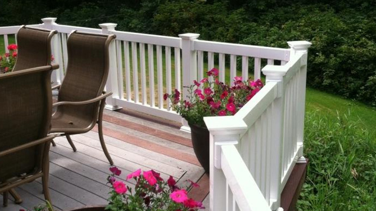 A wooden deck with vinyl railing surrounded by a lush yard features Durables Vinyl Federation Style Post Caps in white