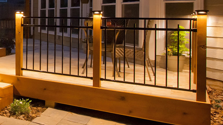 Fortress Flat Pyramid Post Caps with LED light modules illuminate a wood and iron deck railing on a peaceful backyard deck