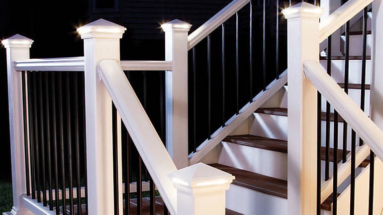 A staircase is illuminated by Pyramid LED Post Cap Lights by Trex Lighting in Classic White