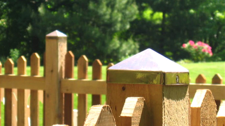 Cedar picket fence has posts topped with pyramid Copper Post Caps