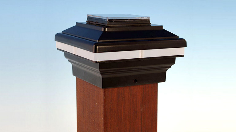 A Zena Solar Post Cap Light by Aurora Deck Lighting in Black sits on a 4x4 post in front of a blue gradient background