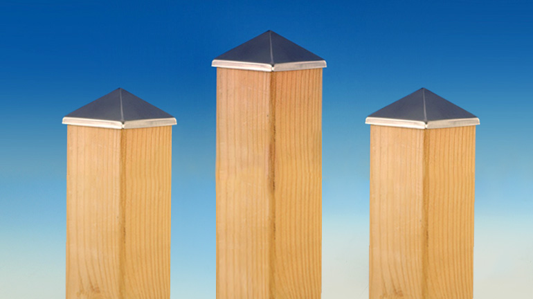 Three 4x4 cedar posts in front of a blue gradient background showcase Aluminum Post Points by Deckorators in a Stainless finish