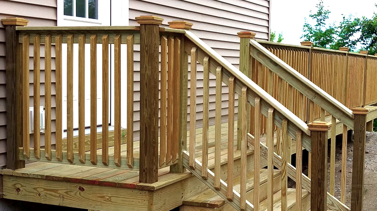 Tan house with wood deck and stairs with wood railing leading down to front yard, all pressure-treaded wood posts are protected with Deckorators Hatteras pressure treated wood post caps