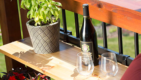 Hold It Mates' Shelf Bracket Bundle is installed on a wood deck with black square aluminum balusters. It is holding a potted plant, wine and two wine glasses.