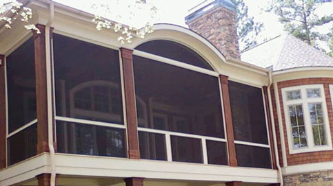 Large screen porch addition to beige house with brick detail features SCREENEZE® to keep pests out