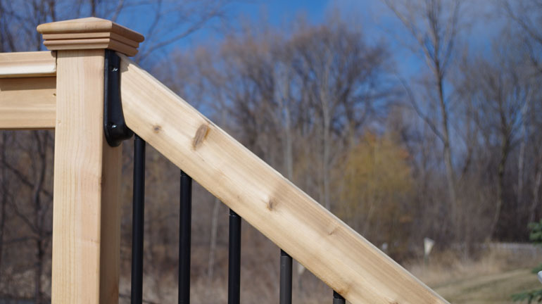Solutions stair rail connector installed into a wood deck rail.