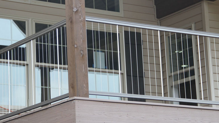 KeyLink Vertical Cable Railing with Bronze top and bottom rails is installed on a cream-colored house, attached to a large 8x8 timber post