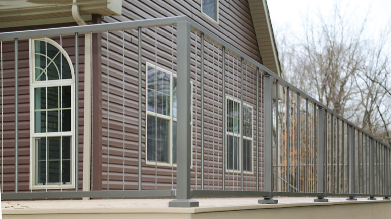Westbury VertiCable with Crossover Posts is installed on a light brown composite deck in front of a brown house