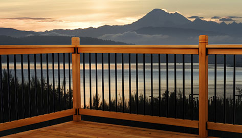 A wood deck that looks out over grey mountains at the end of a sunset. Square black aluminum balusters are sandwiched between wood rails.