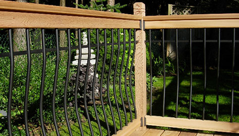Vista's curved metal baluster with wood rail kit is installed on a wood deck on a wooded backyard during mid-day.