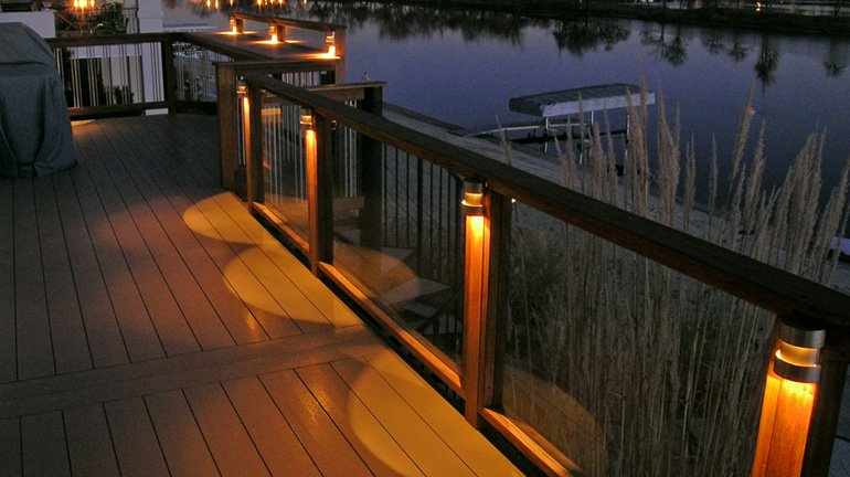 A waterfront deck railing is illuminated with a Highpoint Berkley LED Rail Lights at each post