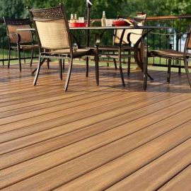 The natural shading of the Fiberon Paramount PVC decking line, shown in Brownstone, complements the beauty of your backyard.
