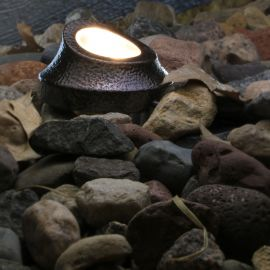 Concealed within the stones of your landscape the Well Pathway Light, shown in Dark Copper Vein, can help illuminate pathways.