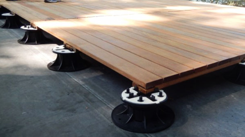 A pooside deck is installed using SE Eterno Adjustable Self-Leveling Pedestal Supports by MRP, enabling pipes and wiring to be conealed below the deck pavers