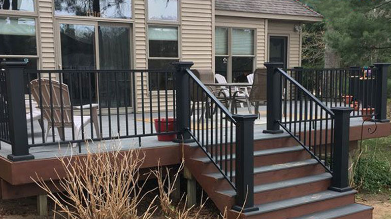 A backyard deck complete with AFCO posts and railings in black