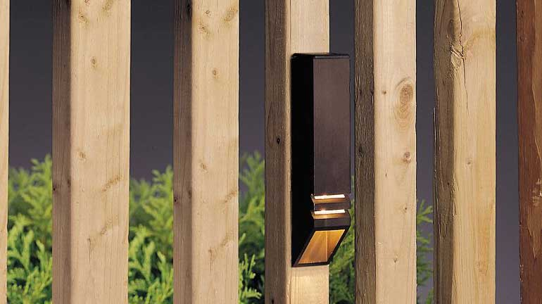 A Kichler rail light on a wooden baluster of deck.