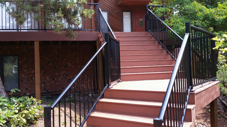 A stairway ascends to a 2nd story composite deck and front door of a home, the deck features black Century Aluminum Picket Railing