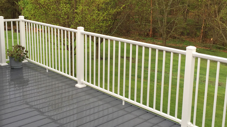 A gray composite deck is enclosed by Dream White Prestige Railing with a green yard and budding trees in the background