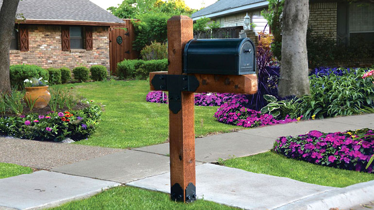 A wood mailbox with OZCO Laredo Sunset Estate Mailbox kit and beatiful flowers in the yard