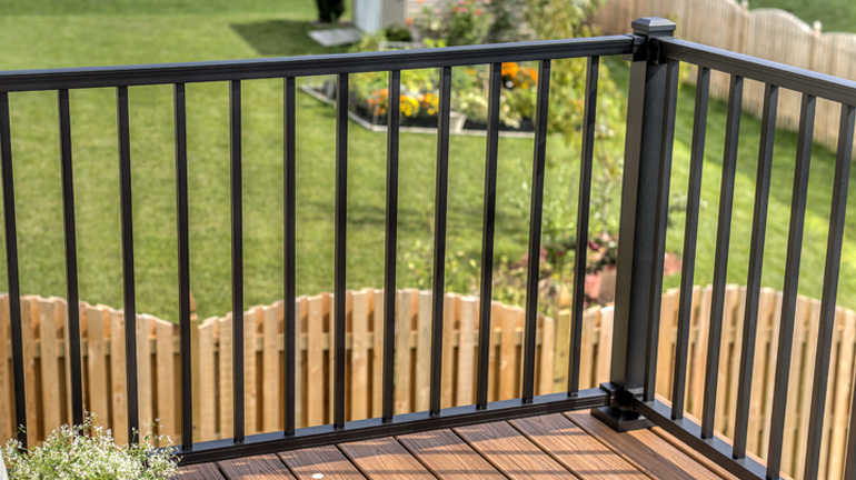 2nd story backyard composite deck overlooks green grass and a flower patch through the square aluminum pickets of the Trex Signature Aluminum Railing System in Charcoal Black
