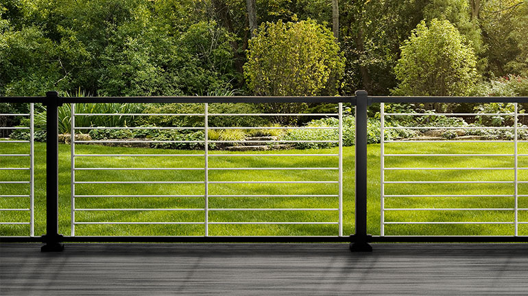 Composite deck with Trex Signature Aluminum Rod Rail in Charcoal Black and Platinum Rods looking out at a grassy yard with trees