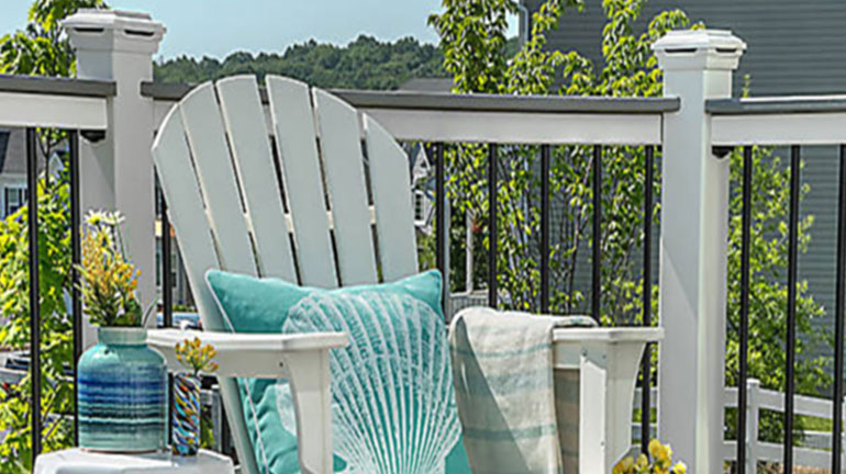 A summer scene with a white patio chair with a Trex Select Deck Railing in the background