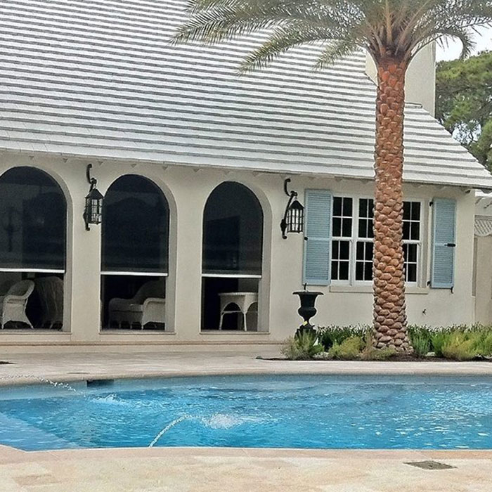 pool next to house with beatiful arched doorways adorned with Insolroll Oasis 2900 window shade system