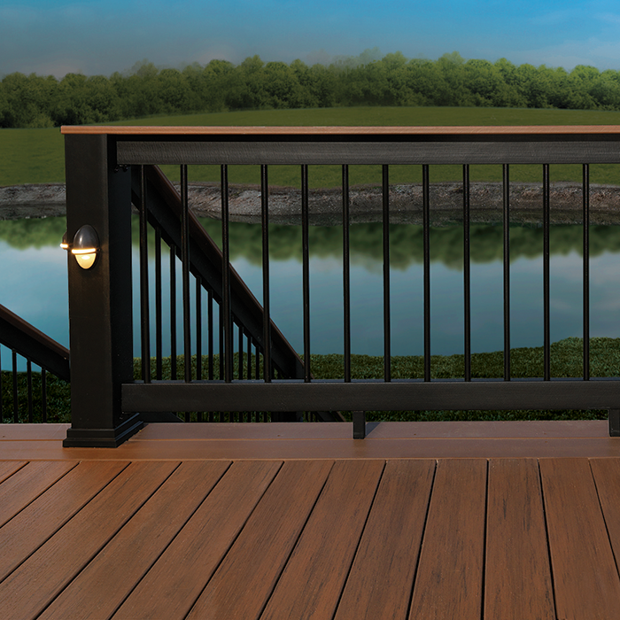 AZEK Evolutions Rail Builder Style in Black with a light brown deck board top rail is installed on a deck overlooking a pond; AZEK Rail Lights in Architechtural Bronze are installed on a Black Evolutions Rail Post Sleeve
