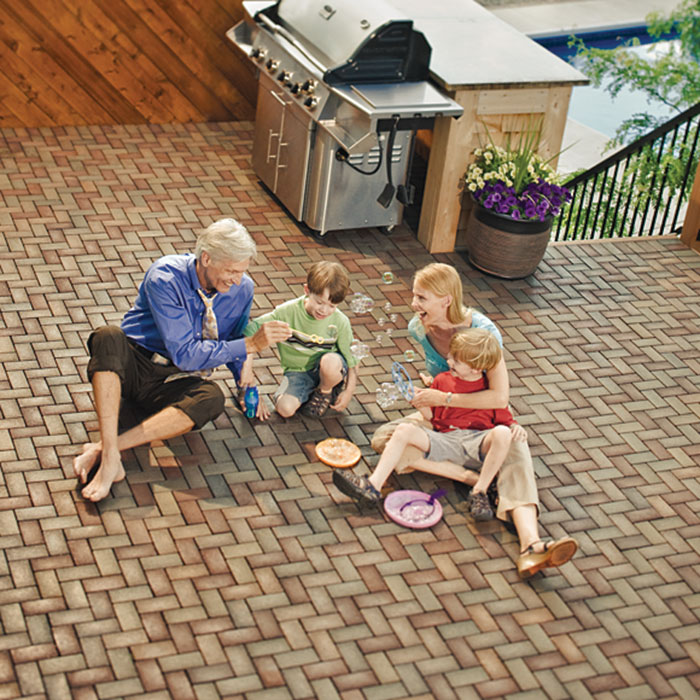 Family sitting on deck made of AZEK pavers blowing bubbles