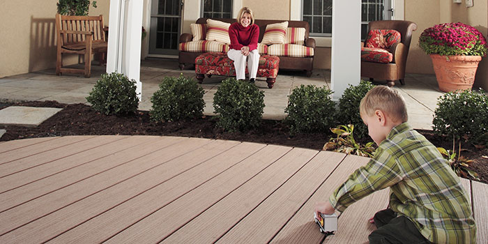 Boy playing on deck with toy truck while mom smiles lovingly