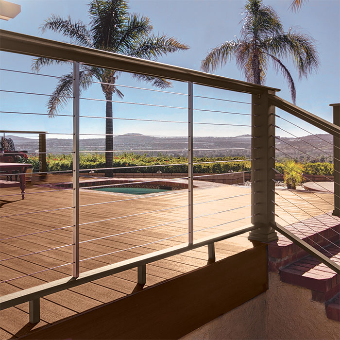 A multi-level deck with expansive views features AZEK Evolutions Rail in Traditional Walnut finish with Cable infill and DeckLites rail lights in Architectural Bronze
