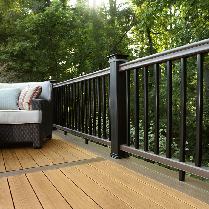A picture-frame style deck with a lounge chair has AZEK TimberTech RadianceRail with Kona rails, Classic Black composite balusters and posts and DeckLites Post Light Modules