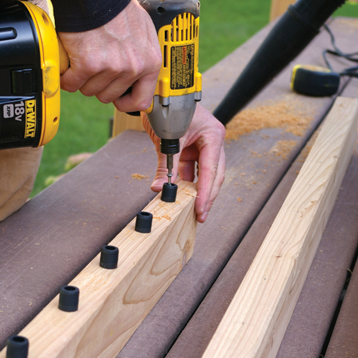 a drill installing the last baluster connector on a cedar railing