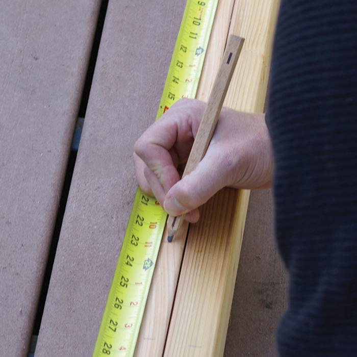 a man is marking the deck railing for balusters to be installed