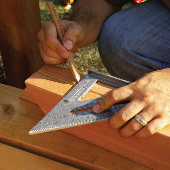 a man using a speed square to mark a cedar stair railing for baluster connectors