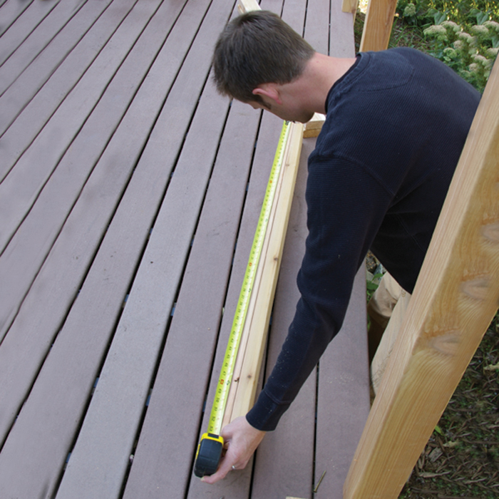a man holds a tape measurer along a cedar deck railing to measure the total distance