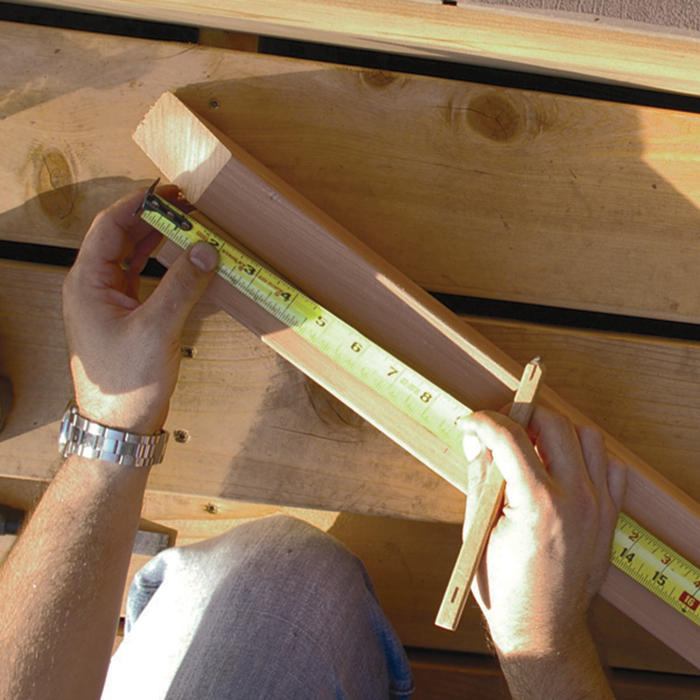 a man with a tape measurer marking cedar stair rails